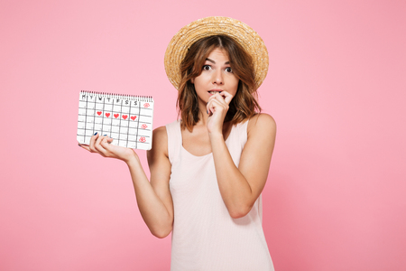 Portrait of embarrassed ?ute girl in summer hat holding calendar with drawn hearts and looking at camera isolated over pink background 版權商用圖片