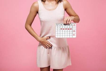 Geerntetes Bild einer jungen Frau im Kleid, das Periodenkalender hält und ihren Bauch lokalisiert über rosa Hintergrund berührt Standard-Bild