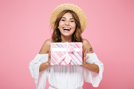 Portrait of a smiling happy girl in summer hat holding gift box and looking at camera isolated over pink background Standard-Bild