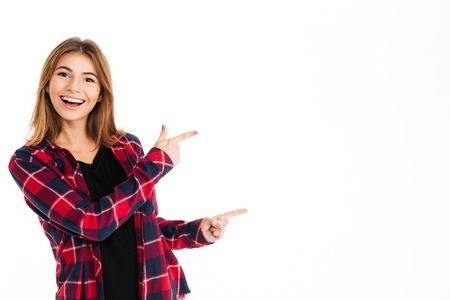 Picture of happy young woman standing isolated over white wall background. Looking camera pointing to copyspace.