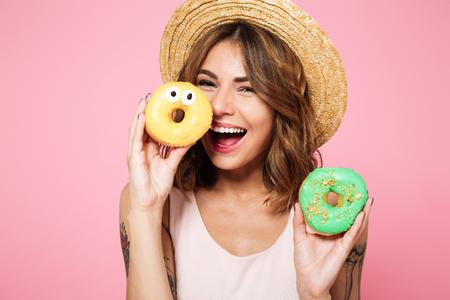 クローズ アップ夏帽子ピンク背景に分離した、彼女の顔にドーナツを持って面白い笑顔の女性の肖像画 写真素材