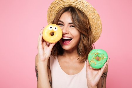 Close up portrait of a funny smiling woman in summer hat holding donut at her face isolated over pink background Stockfoto