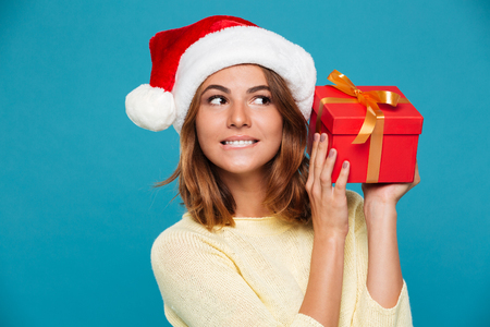 Pleased intrigued woman in sweater and christmas hat holding gift box over blue background