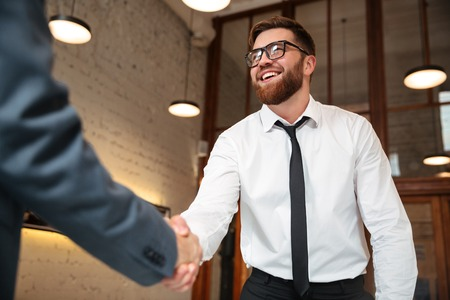 Close up of two young businessmen shaking hands to make a deal indoors Foto de archivo
