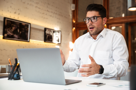 Close-up photo of amazed young businessman in glasses and white shirt looking at laptop screen in office