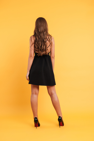 Back view portrait of a young attractive girl with long hair wearing black dress while standing isolated over yellow background Stock fotó