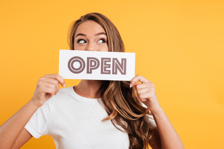 Close up portrait of a pretty girl holding open door sign at her face and looking away isolated over yellow background