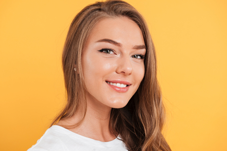 Close up portrait of a pretty smiling girl with long blond hair looking at camera isolated over yellow background Stock Photo