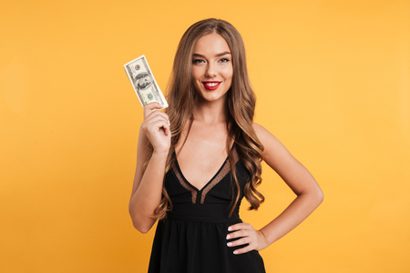 お金紙幣を押し、黄色背景に分離カメラ目線の長いブロンドの髪を持つかなり笑顔少女の肖像画