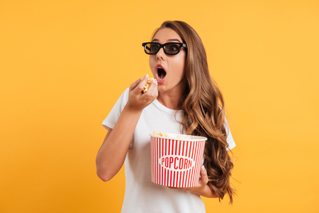 Portrait of an excited girl in 3d glasses holding bucket of popcorn and looking away isolated over yellow background