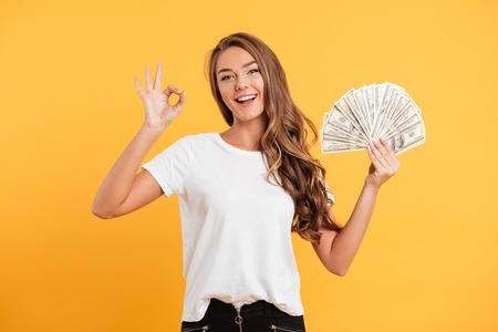Portrait of a cheerful smiling girl holding bunch of money banknotes and showing ok gesture isolated over yellow background