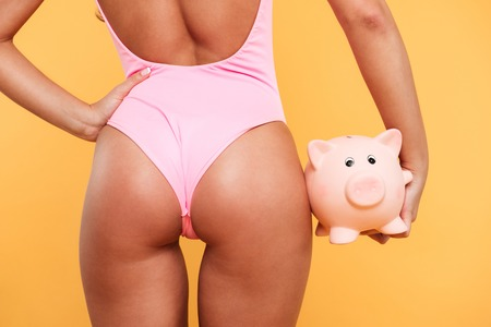Back view close up of womans buttocks in swimsuit with piggy back in hand isolated over yellow background Stock Photo