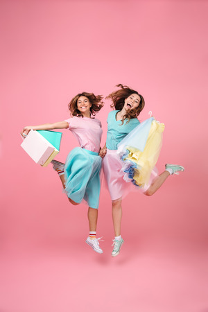 Full length portrait of two joyful pretty girls dressed in bright colorful clothes holding shopping bags and jumping isolated over pink background