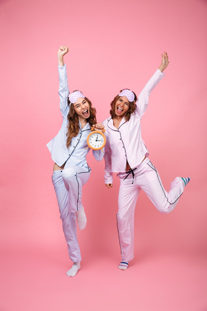 Picture of two funny emotional screaming friends women in pajamas isolated over pink background holding alarm clock. Looking at camera. 스톡 콘텐츠