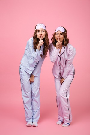 Image of funny displeased two women friends in pajamas isolated over pink background. Looking camera showing silence gesture.