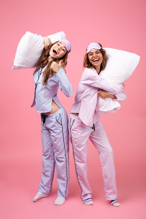 Full length portrait of two happy excited girls dressed in pajamas standing and holding pillows isolated over pink background