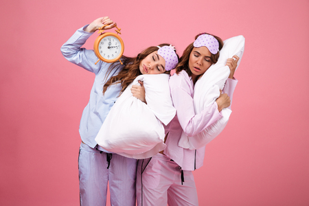 Portrait of two tired pretty girls dressed in pajamas sleeping on pillows while standing and holding alarm clock isolated over pink background