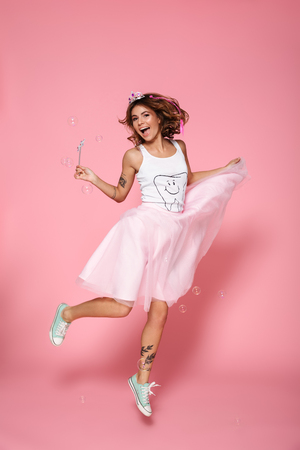Full length portrait of charming princess with magic wand jumping over pink background