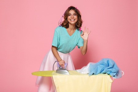 Portrait of a smiling young girl ironing her clothes on a pressboard and showing ok gesture isolated over pink background Foto de archivo