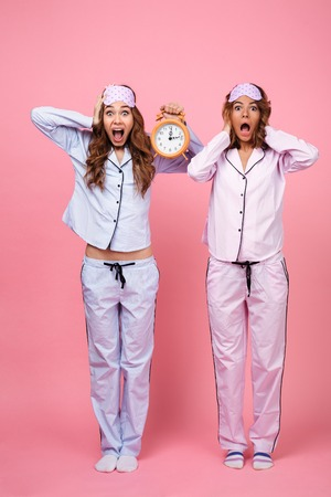 Image of two shocked confused screaming friends women in pajamas isolated over pink background holding alarm clock. Looking camera.