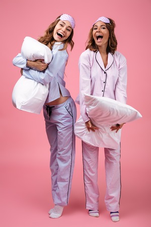 Full length portrait of two cheerful excited girls dressed in pajamas standing and holding pillows isolated over pink background