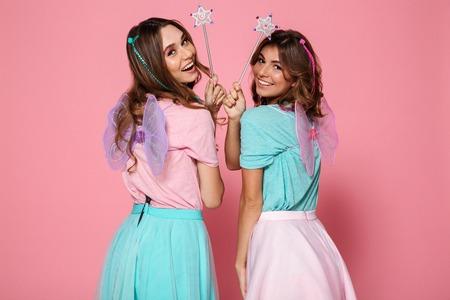 Dos chicas sonrientes vestidas como hadas con alas sosteniendo varitas mágicas mientras miran la cámara por encima del hombro aislado sobre fondo rosa Foto de archivo