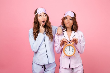 Image of two shocked friends women in pajamas isolated over pink background holding alarm clock. Looking aside. 스톡 콘텐츠