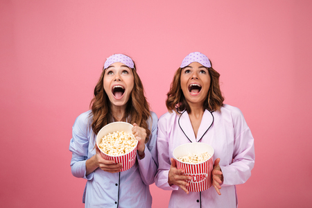 Two happy cheerful girls dressed in pajamas holding popcorn and looking up at copy space isolated over pink background