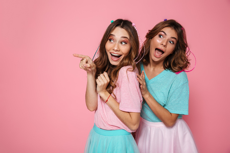 Two funny brunette woman in colorful tshirts pointing with finger, looking aside, isolated on pink background