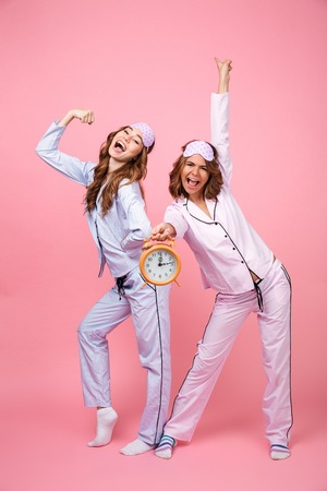 Photo of two happy funny friends women in pajamas isolated over pink background holding alarm clock. Looking camera.