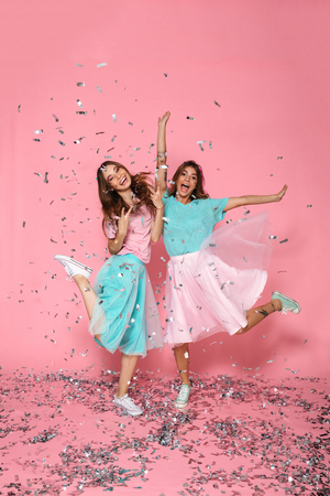 Full length portrait of two pretty girls dressed like princess having fun with sequins, isolated over pink background