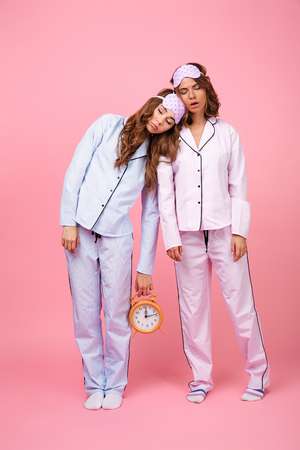 Photo of two friends women in pajamas isolated over pink background sleeping holding alarm clock.