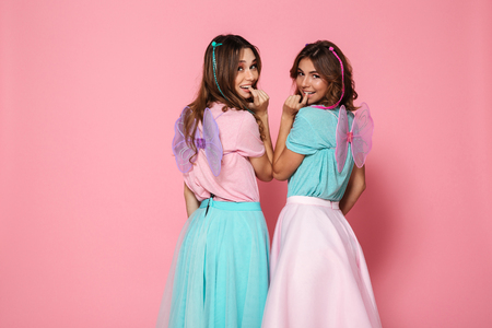 Two pretty smiling girls dressed like fairies with wings looking at camera over shoulder isolated over pink background
