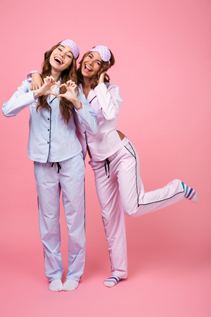 Photo of pretty two girls friends in pajamas isolated over pink background. Looking camera showing heart love gesture.
