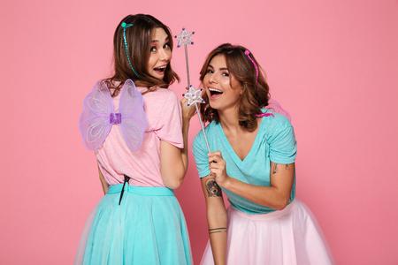 ピンクの背景の上に孤立した肩の上にカメラを見ながら、魔法の杖を持つ翼を持つ妖精のような服を着た2人の陽気な若い女の子 写真素材