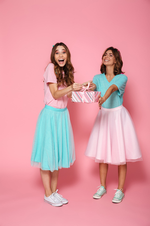 Full length photo of two overjoyed young woman dressed like children exchanging presents, isolated over pink background
