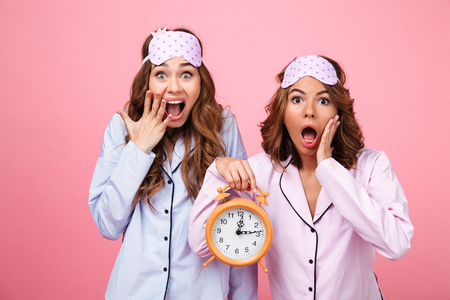 Picture of two shocked friends women in pajamas isolated over pink background holding alarm clock. Looking camera.