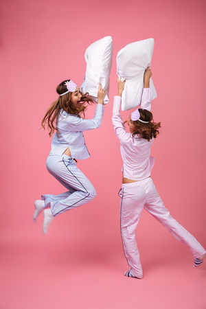 Full length portrait of two excited pretty girls dressed in pajamas having pillow fight isolated over pink background