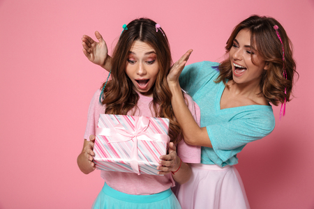 Young amazed woman holding present while celebrating birthday with her female friend, isolated over pink background