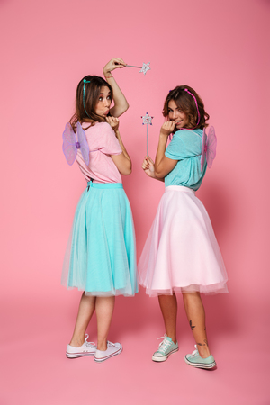 Full length portrait of a two smiling happy girls dressed like fairies with wings holding magic wands while looking at camera over shoulder isolated over pink background