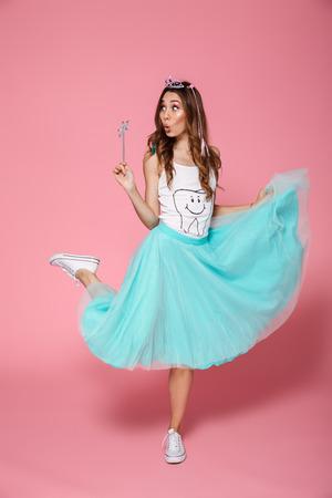 Foto in voller Länge des überraschten hübschen Mädchens in der Krone, die den magischen Stab, beiseite schauend bei der Stellung auf einem Bein, lokalisiert über rosa Hintergrund hält