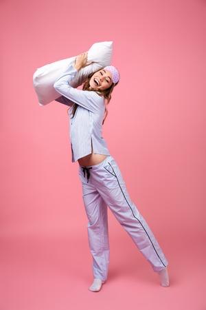 ピンクの背景に隔離されたカメラを見ながら、枕を抱えてパジャマに身を包んだ陽気な少女の全長の肖像画