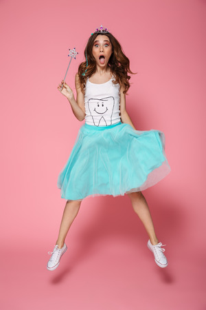 Full length photo of shocked pretty woman in crown holding magic wand while jumping over pink background