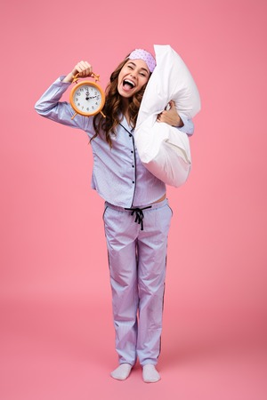 Portrait of a cheerful funny girl dressed in pajamas holding pillow and showing alarm clock isolated over pink background 版權商用圖片