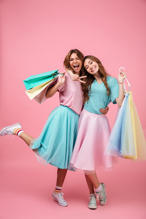 Full length portrait of two happy smiling girls dressed in bright colorful clothes holding shopping bags isolated over pink background