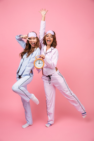 Photo of two pretty funny friends women in pajamas isolated over pink background holding alarm clock. Looking camera.