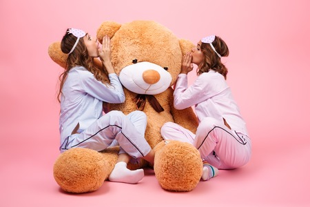 Two girls dressed in pajamas sitting with a big teddy bear and whispering a secret isolated over pink Stock fotó