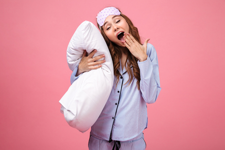 Portrait of a tired pretty girl dressed in pajamas holding pillow and yawning isolated over pink background 免版税图像