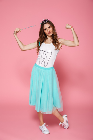 Full length portrait of funny young woman dressed like princess holding magic wand, showing her small muscles, looking at camera, isolated on pink background