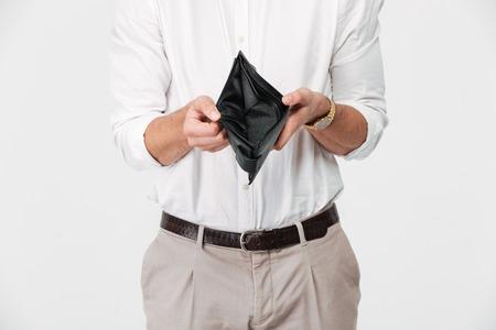 白い背景の上に隔離された空の財布を示す男のクローズアップ肖像画